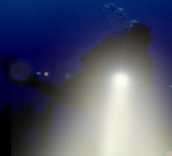 Night diver with flashlight on